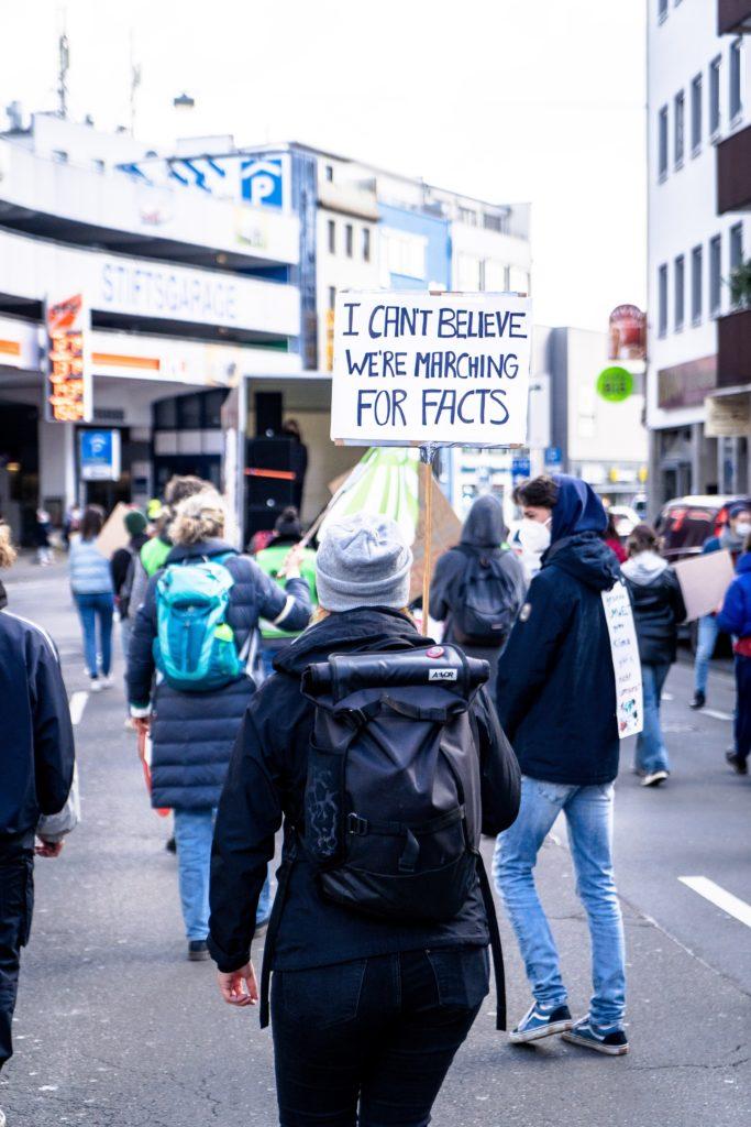 "Demo mit Menschen und Plakat ""I CAN'T BELIEVE WE'RE MARCHING FOR FACTS"""